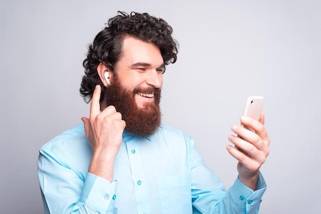 Homem feliz e alegre com barba casual usando erapods e olhando para o smartphone sobre uma parede branca