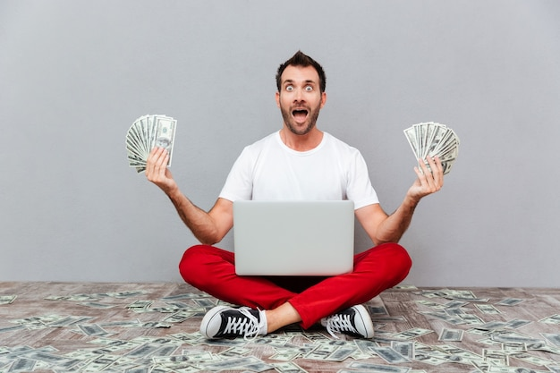 Homem feliz e animado casual sentado no chão com o laptop e segurando dinheiro sobre um fundo cinza