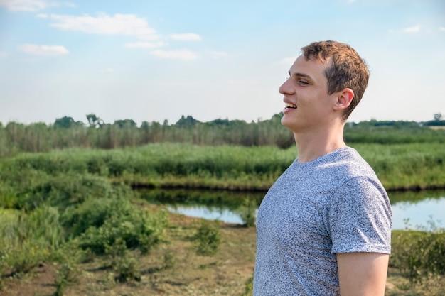 Homem feliz e casual curtindo e relaxando em pé em um campo com um lago ao fundo