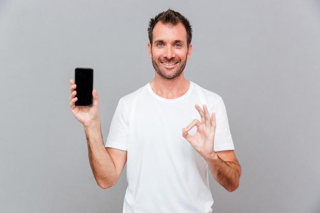 Homem feliz e casual mostrando a tela do smartphone em branco e um gesto de aprovação sobre um fundo cinza