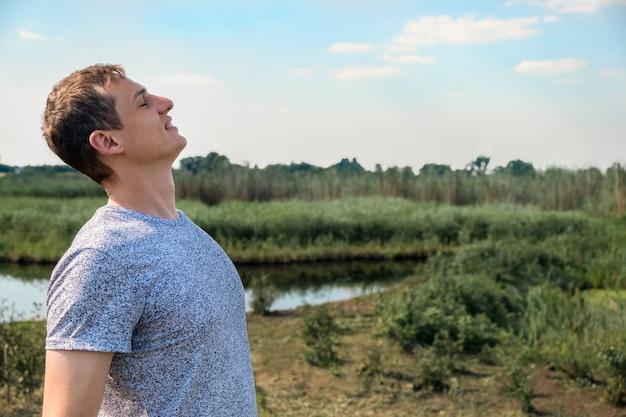 Homem feliz e casual respirando ar fresco em um campo com um lago ao fundo