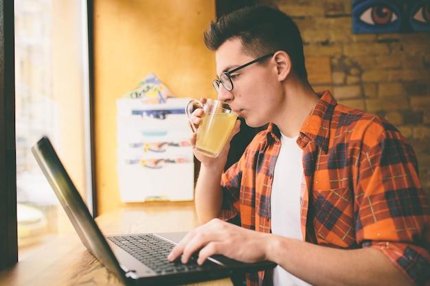 Homem feliz e casual usando laptop em um café