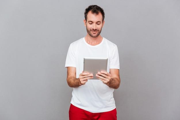 Homem feliz e casual usando um computador tablet isolado em um fundo cinza
