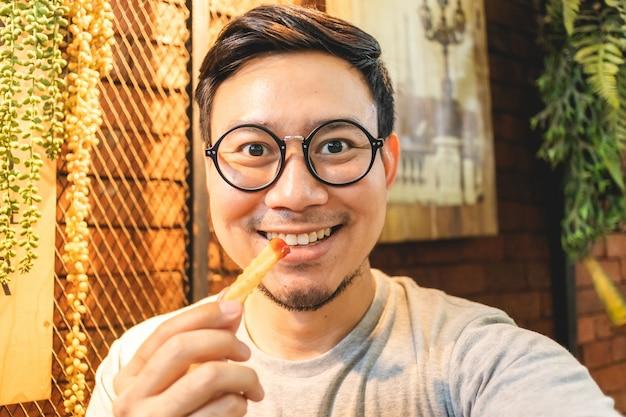 Homem feliz é comer batatas fritas no café.