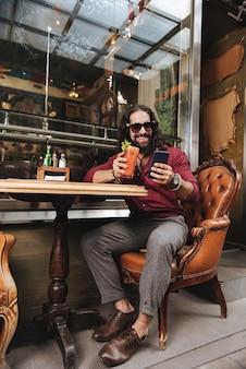Homem feliz e encantado sorrindo enquanto desfruta de seu descanso no café