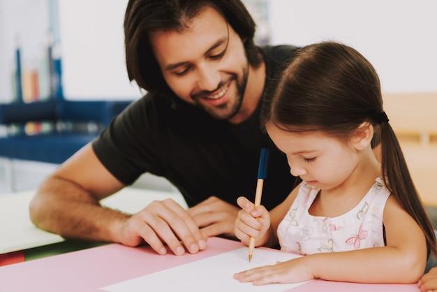 Homem feliz e filha desenhar na clínica pediátrica