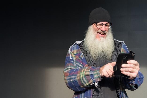 Homem feliz e maduro barbudo moderno usando o telefone contra uma parede preta