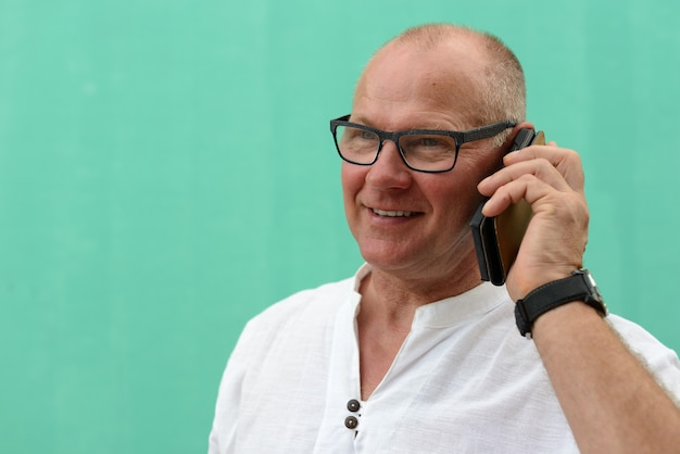 Homem feliz e maduro turista bonito falando ao telefone contra uma parede verde ao ar livre