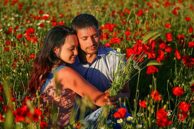 Homem feliz e mulher abraçando em um campo de papoulas.