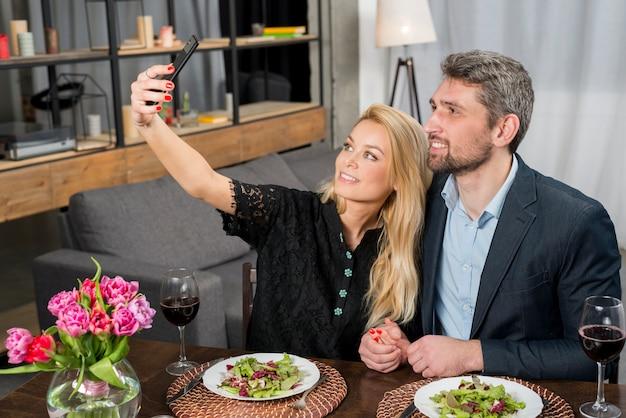 Homem feliz e mulher alegre tomando selfie no smartphone na mesa