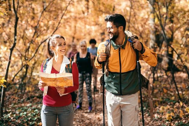 Homem feliz e mulher, caminhadas na floresta no outono. mulher segurando o mapa e o homem olhando para ela e sorrindo. no fundo outros caminhantes andando.