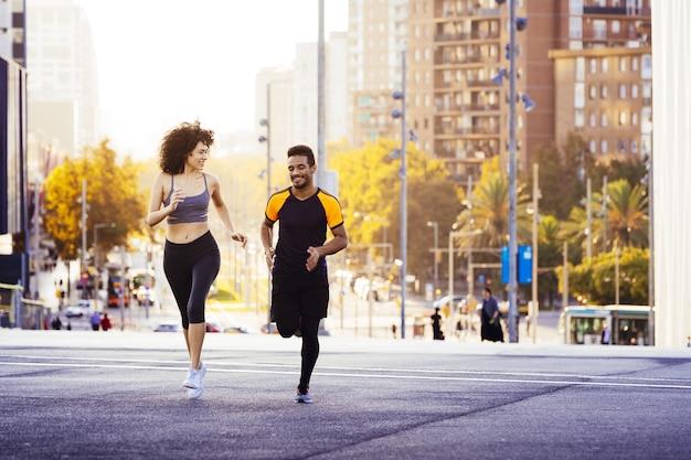 Homem feliz e mulher esportiva correndo na cidade