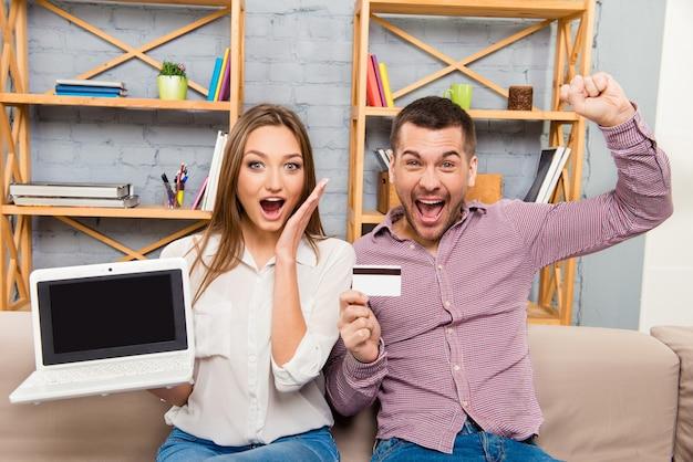 Homem feliz e mulher gritando com laptop e cartão do banco