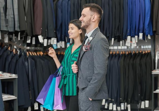 Homem feliz e mulher segurando sacolas de compras, posando.