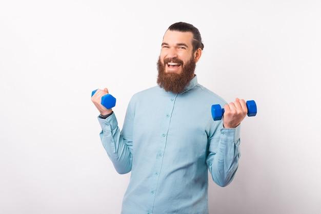 Homem feliz e positivo está levantando alguns halteres pequenos.