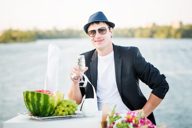 Homem feliz e positivo, o noivo de chapéu e terno tem nas mãos uma taça de champanhe durante o registro de casamento