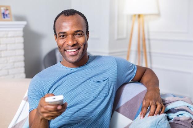 Homem feliz e simpático, sentado em frente à tela da tv e segurando o controle remoto enquanto descansa no sofá