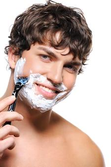 Homem feliz e sorridente barbeando o rosto