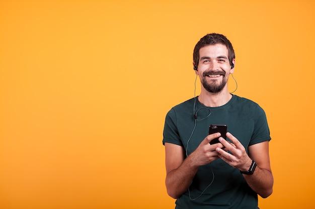 Homem feliz e sorridente com fones de ouvido na escuta de música em seu smartphone, isolado em fundo amarelo. estilo de vida de entretenimento móvel