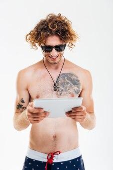 Homem feliz e sorridente com óculos escuros e shorts de praia usando tablet pc isolado sobre uma parede branca