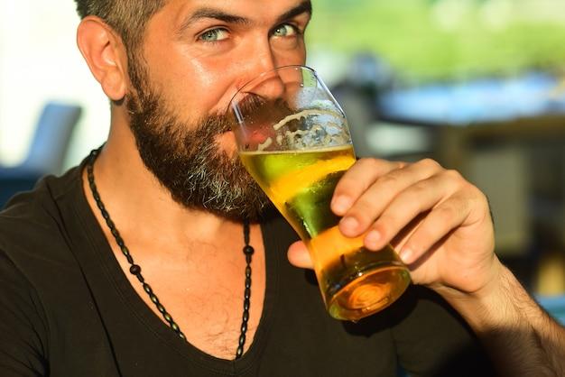 Homem feliz e sorridente com uma caneca grande de cerveja na mão