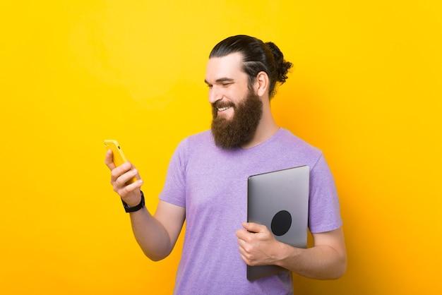 Homem feliz e sorridente está olhando para o telefone enquanto segura seu laptop.