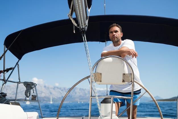 Homem feliz e sorridente navegando com seu iate no mar