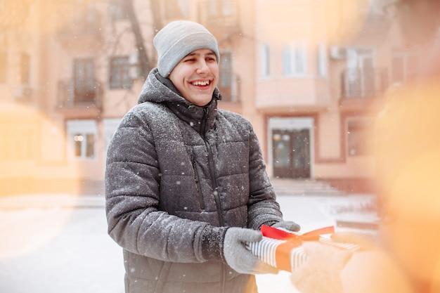 Homem feliz e sorridente recebe um presente da namorada no dia dos namorados em um parque de inverno nevado. um jovem macho recebe um presente ao ar livre em um dia frio de inverno. férias e conceito de presentes.
