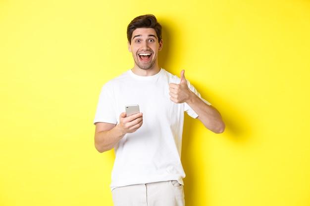 Homem feliz e sorridente segurando o smartphone, aparecendo o polegar em aprovação, recomendar algo online, em pé sobre um fundo amarelo.
