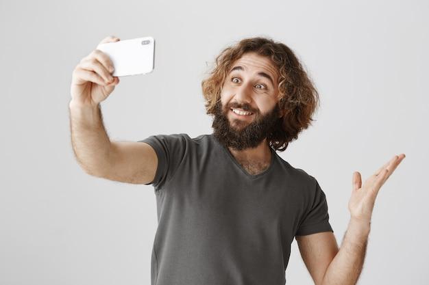 Homem feliz e sorridente tirando uma selfie na frente da cidade