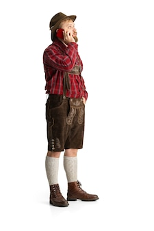 Homem feliz e sorridente vestido em traje tradicional da baviera, com comida festiva. comemoração, oktoberfest, conceito de festival. copie o espaço para o anúncio