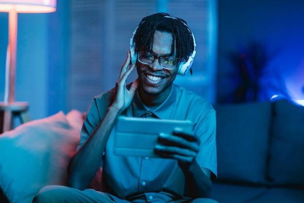 Homem feliz em casa usando tablet e fones de ouvido