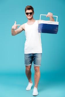 Homem feliz em cima apontando azul isolado