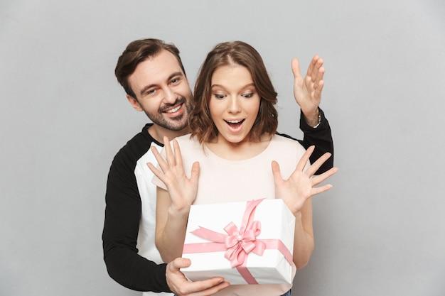 Homem feliz em pé isolado segurando a caixa de presente para sua mulher.