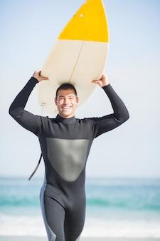 Homem feliz em roupa de mergulho carregando prancha sobre a cabeça