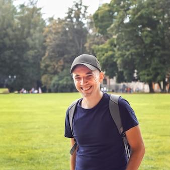 Homem feliz em roupas esportivas no parque. um jovem com uma mochila caminha em um dia claro de verão. o homem sorri. boné. relva. árvores. andar. estilo de vida. copie o espaço.