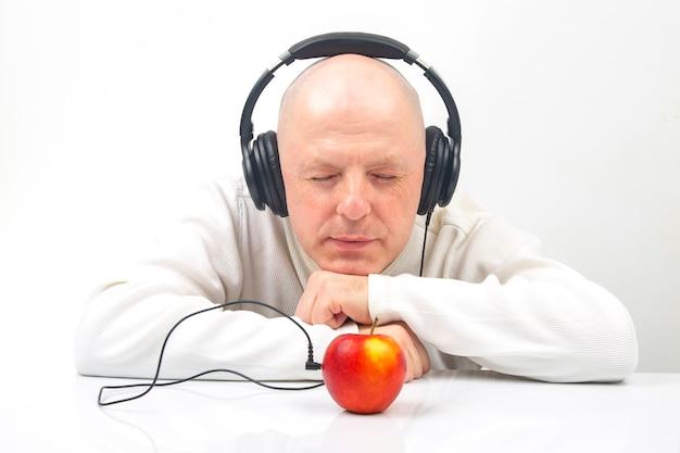 Homem feliz em roupas leves, usando fones de ouvido portáteis de tamanho normal, ouve música usando um reprodutor de maçã.