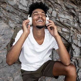 Homem feliz em tiro médio usando fones de ouvido
