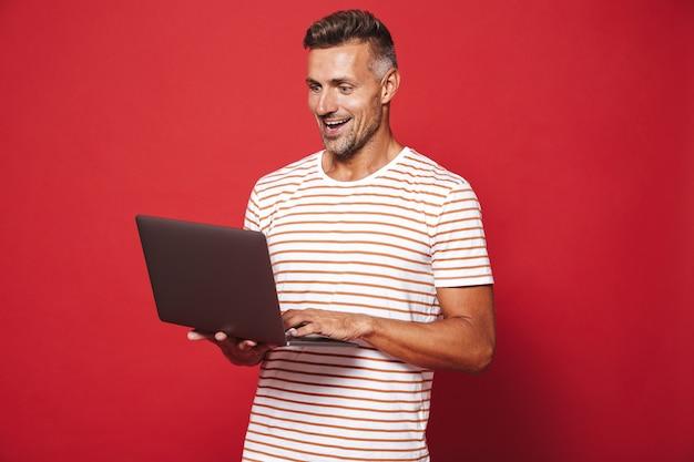 Homem feliz em uma camiseta listrada sorrindo enquanto segura e usa laptop isolado no vermelho
