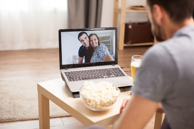 Homem feliz em ver seus amigos durante uma videochamada em tempo de pandemia global.