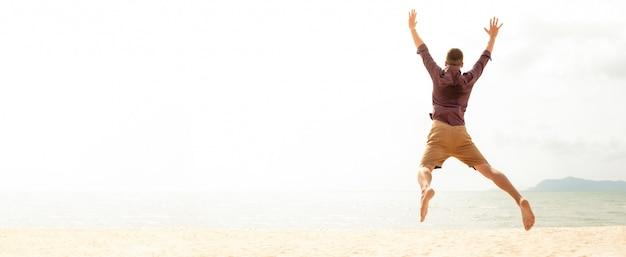 Homem feliz energético pulando na praia nas férias de verão