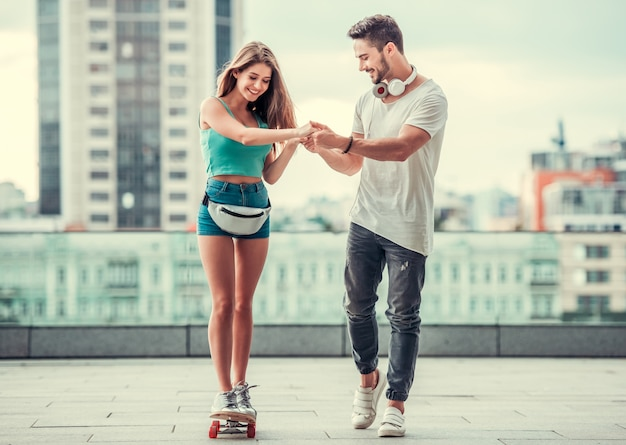 Homem feliz ensina menina a andar de skate na rua. jovem alegre e jovem se divertem juntos.