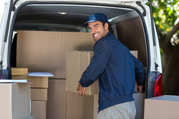 Homem feliz entrega carregando caixa de papelão na van