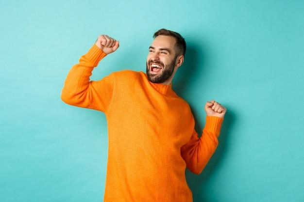 Homem feliz erguendo o braço, sentindo-se vencedor, triunfando e comemorando, em pé sobre a parede turquesa clara.
