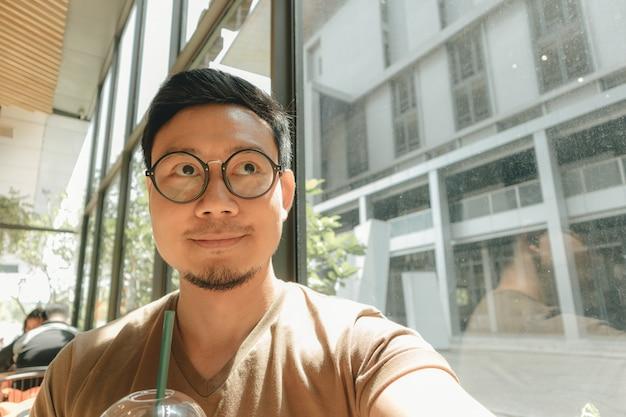 Homem feliz está bebendo café gelado no café esconder do sol quente e brilhante.