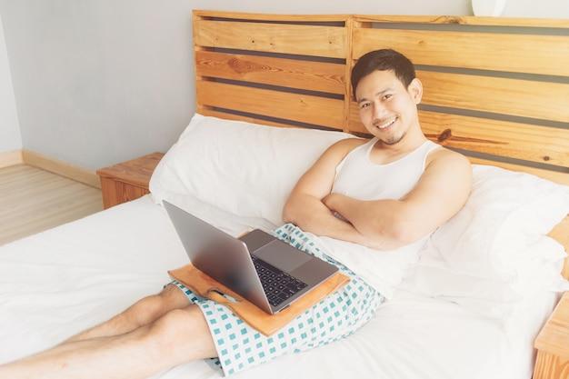 Homem feliz está trabalhando com seu laptop na cama dele.