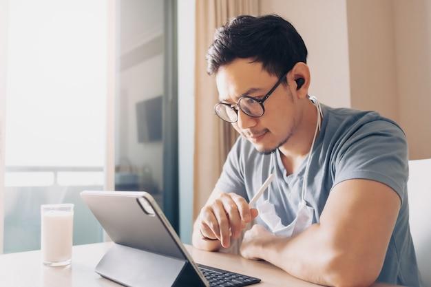 Homem feliz está trabalhando em seu tablet no conceito de trabalho em casa