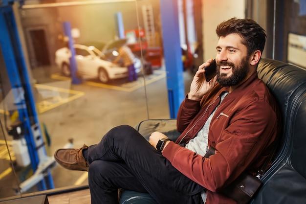 Homem feliz falando em um smartphone, sentado no sofá, enquanto um técnico automotivo conserta seu carro