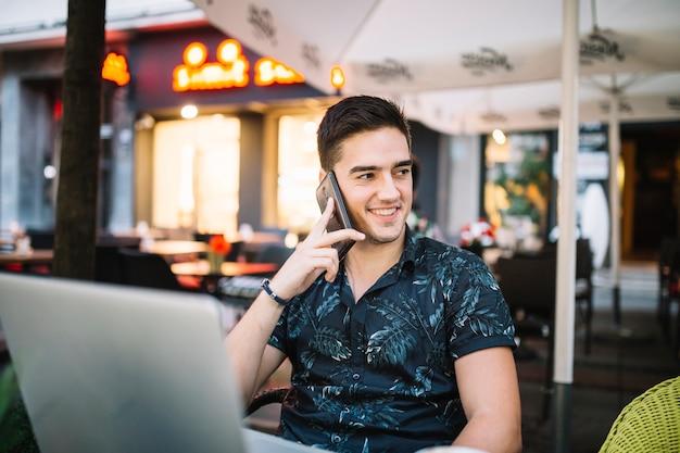 Homem feliz falando no smartphone no café