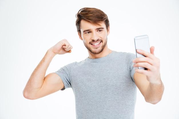 Homem feliz fazendo foto de selfie no smartphone e mostrando o bíceps isolado em um fundo branco